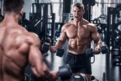 Muskulös man som utarbetar i idrottshall, kroppsbyggare stark absmanlig arkivbilder