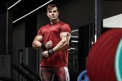 Muskulös man som utarbetar i idrottshall, stark kroppsbyggareman arkivbild