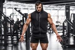 Muskulös man som utarbetar i idrottshall, stark manlig kroppsbyggare royaltyfri fotografi