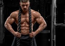 Muskulös man som utarbetar i idrottshallen som gör övningar royaltyfria foton