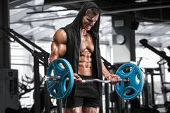 Muskulös man som utarbetar i idrottshallen som gör övningar med skivstången för biceps, stark manlig naken torsoabs arkivbild