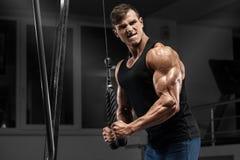 Muskulös man som utarbetar i idrottshallen som gör övningar på triceps, stark man royaltyfri fotografi