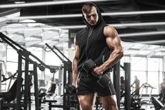 Muskulös man som utarbetar i idrottshallen som gör övningar, stark manlig kroppsbyggare royaltyfri bild