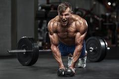 Muskulös man som utarbetar i idrottshallen som gör övningar, stark manlig naken torsoabs arkivfoton