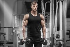 Muskulös man som utarbetar i idrottshallen som gör övningar, stilig stark man royaltyfria bilder