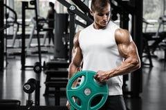 Muskulös man som utarbetar i idrottshallen som gör exercisess, stark manlig kroppsbyggare fotografering för bildbyråer
