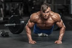Muskulös man som utarbetar i idrottshallen som gör skjuta-UPS övningar, stark manlig naken torsoabs arkivbilder