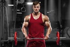 Muskulös man som utarbetar i idrottshallen som gör övningar med skivstången, stark man royaltyfri foto