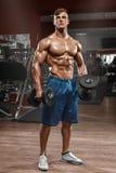 Muskulös man som utarbetar i idrottshallen som gör övningar med skivstången, stark manlig naken torsoabs royaltyfri foto