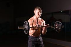 Muskulös man som utarbetar i idrottshallen som gör övningar med skivstången, stark manlig naken torsoabs royaltyfria bilder