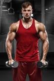 Muskulös man som utarbetar i idrottshallen som gör övningar, stark man fotografering för bildbyråer