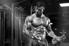 Muskulös man som utarbetar i idrottshallen som gör övningar, stark manlig naken torsoabs royaltyfri foto