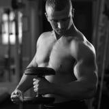 Muskulös man som utarbetar med hantlar i idrottshall arkivfoton