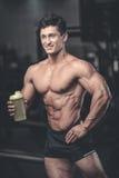 Muskulös man som vilar efter övning och dricker från shaker royaltyfri bild