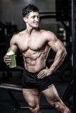 Muskulös man som vilar efter övning och dricker från shaker arkivfoton