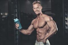Muskulös man som vilar efter övning och dricker från shaker royaltyfria bilder