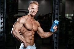 Muskulös man som vilar efter övning och dricker från shaker royaltyfri fotografi