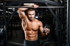 Muskulös man som vilar efter övning och dricker från shaker Arkivfoto