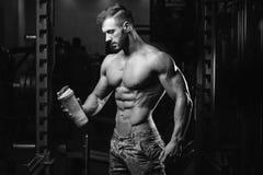 Muskulös man som vilar efter övning och dricker från shaker arkivbild
