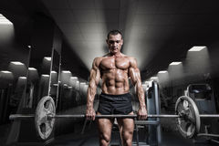Muskulös mangenomkörare med skivstången på idrottshallen Deadlift skivstångarbete Royaltyfri Foto