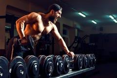 Muskulös manlig kroppsbyggare som utarbetar i idrottshall arkivbilder