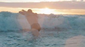 Muskulös mansimning i havet i ultrarapid på solnedgången stock video