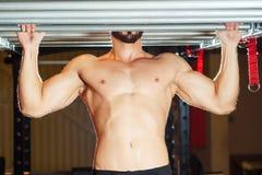 Muskulös passformman för idrottsman nen som drar upp på horisontalstång i en idrottshall Fotografering för Bildbyråer