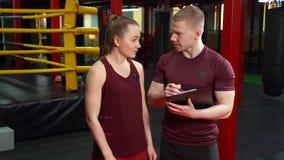 Muskulös personlig lagledare som skriver på skrivplattan och diskuterar utbildningsplanet till den unga kvinnan i idrottshall för stock video