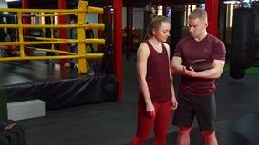 Muskulös personlig lagledare som skriver på skrivplattan och talar till den unga kvinnan i idrottshall för arg utbildning arkivfilmer