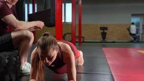 Muskulös personlig lagledare som skriver på skrivplattan och talar till den unga kvinnan i idrottshall för arg utbildning lager videofilmer