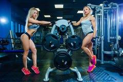 Muskulös sexig kvinnakvinna för kondition som två kopplar av i idrottshallen sund livsstil för begrepp Kroppsbyggare i idrottshal royaltyfri foto