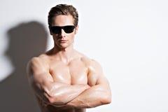 Muskulös sexig man i exponeringsglas med korsade armar Arkivfoton