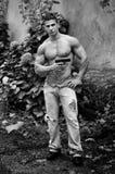 Muskulös shirtless ung man med ett vapen i hans hand Royaltyfri Fotografi