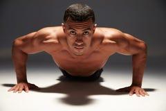 Muskulös shirtless ung man som gör press-UPS Royaltyfri Foto