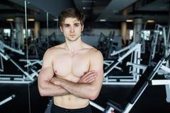 Muskulös shirtless ung man som vilar i idrottshall under genomköraren som visar den muskulösa torson, pecs och abs i spegeln på i Arkivfoton