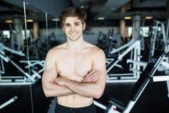 Muskulös shirtless ung man som vilar i idrottshall under genomköraren som visar den muskulösa torson, pecs och abs i spegeln på i Arkivbilder