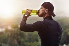 Muskulös skäggig idrottsman nendrink som ett vatten efter bra genomkörareperiod på stad parkerar royaltyfria foton
