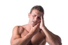 Muskulös stilig man som rymmer hans huvud med för royaltyfri bild