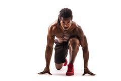 Muskulös svart man som är klar att sprinta, och körning royaltyfri fotografi