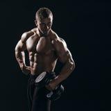Muskulös torsoman med hanteln på svart bakgrund i studio fotografering för bildbyråer