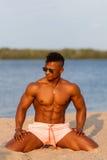 Muskulös ung idrotts- sexig man på stranden med en naken torso i underkläder Varm svart härlig grabb, konditionmodell med ett ran Fotografering för Bildbyråer