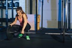 Muskulös ung konditionkvinna som lyfter en viktcrossfit i idrottshallen Skivstång för konditionkvinnadeadlift Idrottshallen på de Royaltyfri Bild