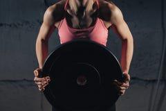 Muskulös ung konditionkvinna som lyfter en viktcrossfit i idrottshallen Skivstång för konditionkvinnadeadlift Idrottshallen på de Royaltyfria Bilder