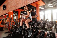 Muskulös ung kvinna med den härliga kroppen som gör övningar med hanteln royaltyfri bild