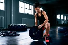 Muskulös ung kvinna som sätter skurkrollvikter för övning royaltyfri foto