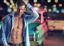 Muskulös ung man med den retro bilen Arkivfoton