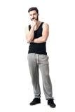 Muskulös ung man som bär den svarta undertröjan med handen på hakan fotografering för bildbyråer