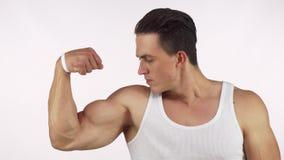 Muskulös ung man som böjer hans bicep som häftigt ser till kameran lager videofilmer