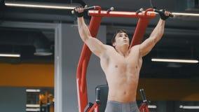 Muskulös ung man som drar upp i en idrottshall, slut upp Royaltyfri Fotografi