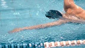 Muskulös yrkesmässig manlig simmare i skyddsglasögon som har utbildning som gör krypandeslaglängden lager videofilmer